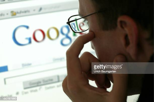 Man in front of a display with the website of the internet search engine Google