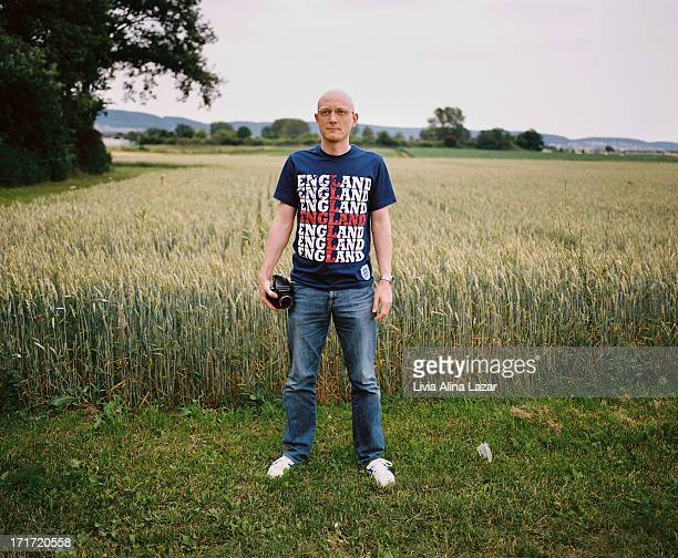 CONTENT] Man in front of a field wearing an England tshirt and holding a film camera