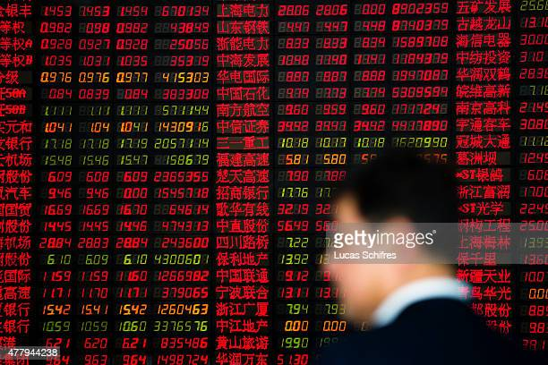 A man in front of a Stock Exchange board in Shenyin and Wanguo Securities' brokerage house on May 12 in Shanghai China In China home of the Shanghai...