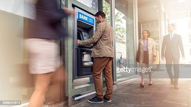 man in front of an atm machine - bank financial building stock pictures, royalty-free photos & images