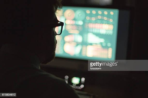 Man in front of computer monitor, working