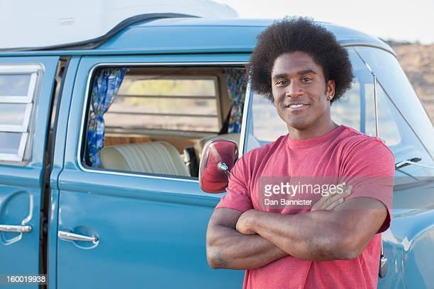 Man in front of his mini van during road trip
