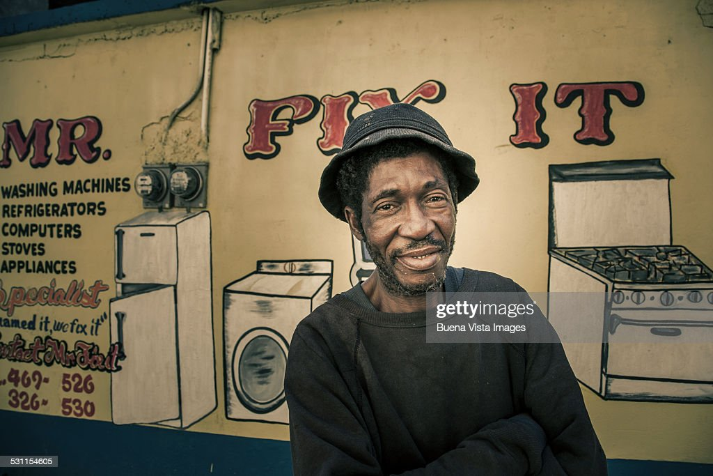 Man in front of his repair shop : Stock Photo