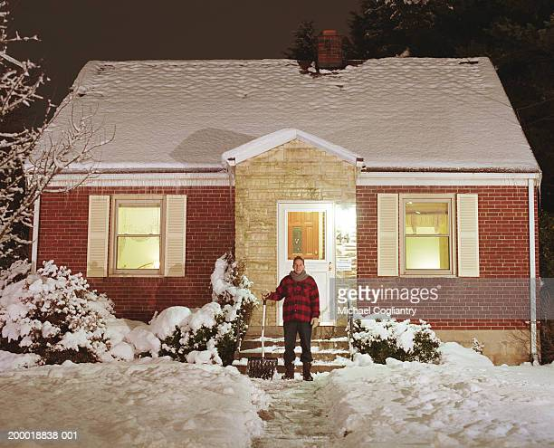 Man in front of house with snow shovel
