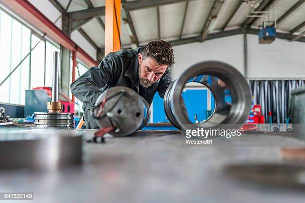 Man in front of hydraulic cylinder