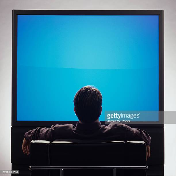 man in front of large blank television screen - 大型テレビ ストックフォトと画像