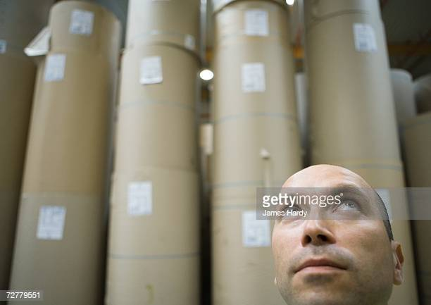 Man in front of rolls of paper in warehouse