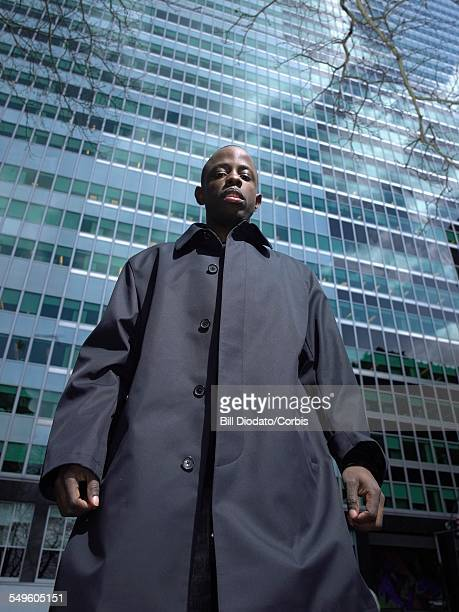 man in front of skyscraper - トレンチコート ストックフォトと画像