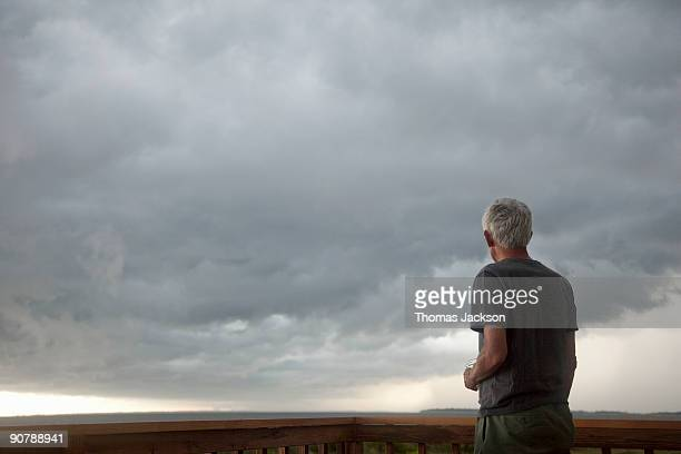 man in front of stormy skies - ominous stock pictures, royalty-free photos & images