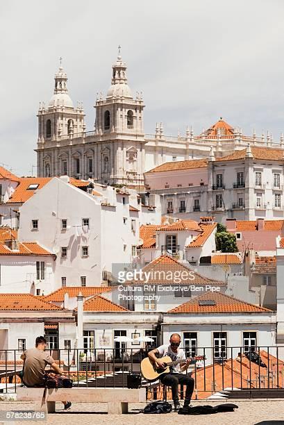 Man in front of the Monastery of Sao Vicente De Fora playing guitar, Lisbon, Portugal
