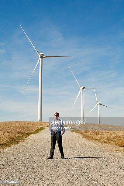 homme en face de turbines de vent - front view photos et images de collection