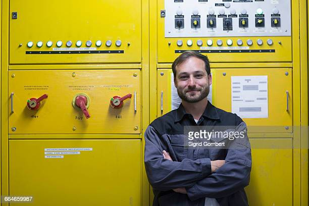 Man in front of yellow control panel, arms crossed smiling