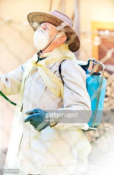 Uomo in abiti di protezione Spruzzare sostanze chimiche completo