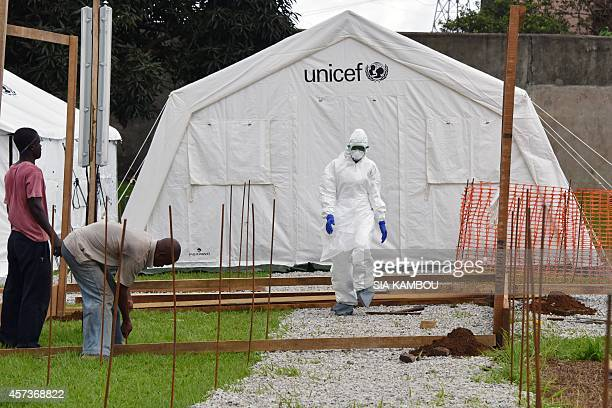 A man in full protective gear passes in front of workers building a tent in the Ebola treatment unit being preventively set to host potential Ebola...