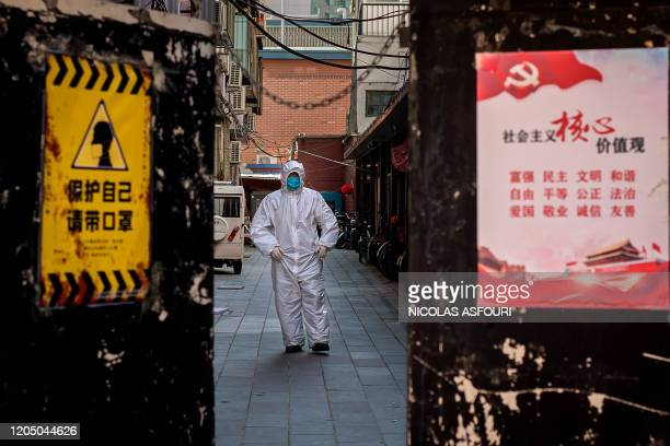 A man in full protective gear to prevent from the spread of the COVID19 coronavirus is seen outside a residential building where a person has been...