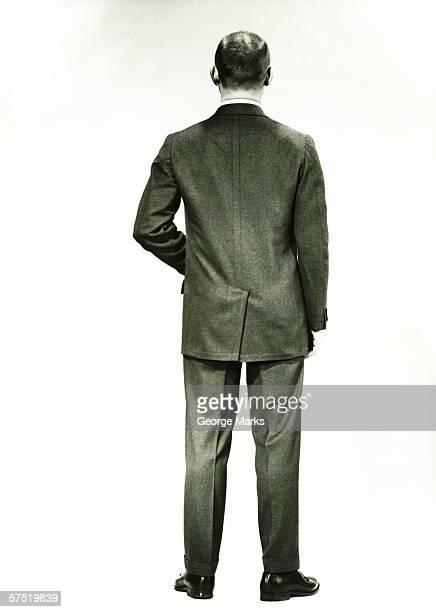 Man in full suit standing in studio, (Rear view), (B&W)