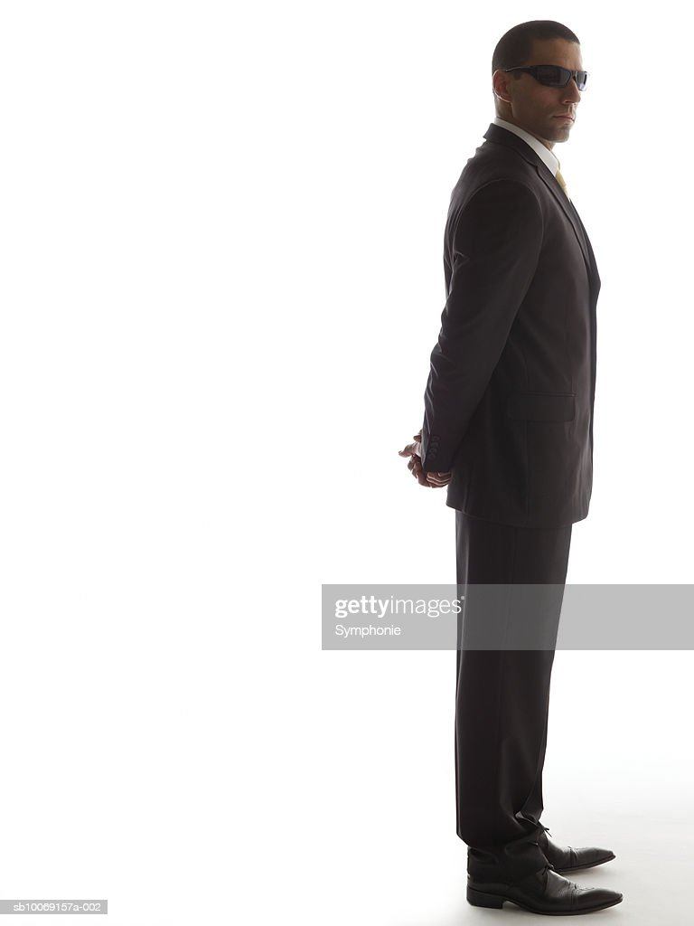 Man in full suit standing with his hands back, side view : Stockfoto