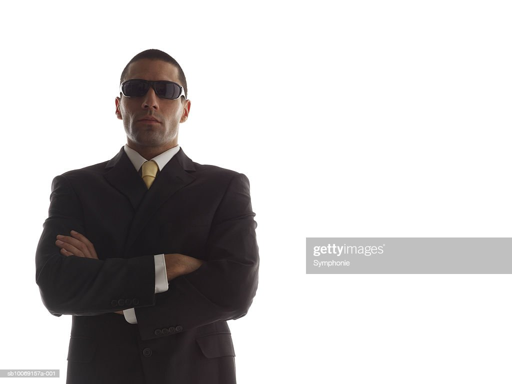 Man in full suit wearing sunglasses, arms crossed, portrait : Stockfoto