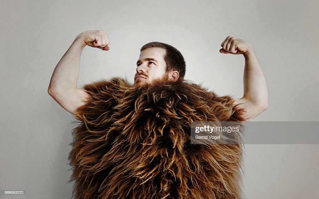 Man in fur suit flexing : Stock Photo