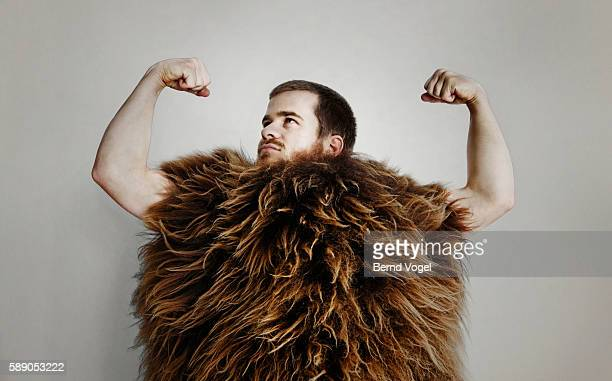 man in fur suit flexing - caveman stock photos and pictures