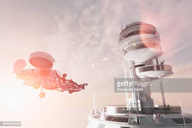 man in futuristic tower waving to flying vehicle - space station stock pictures, royalty-free photos & images