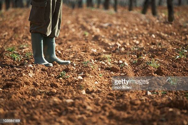 Man in galoshes standing on brown soil, low section