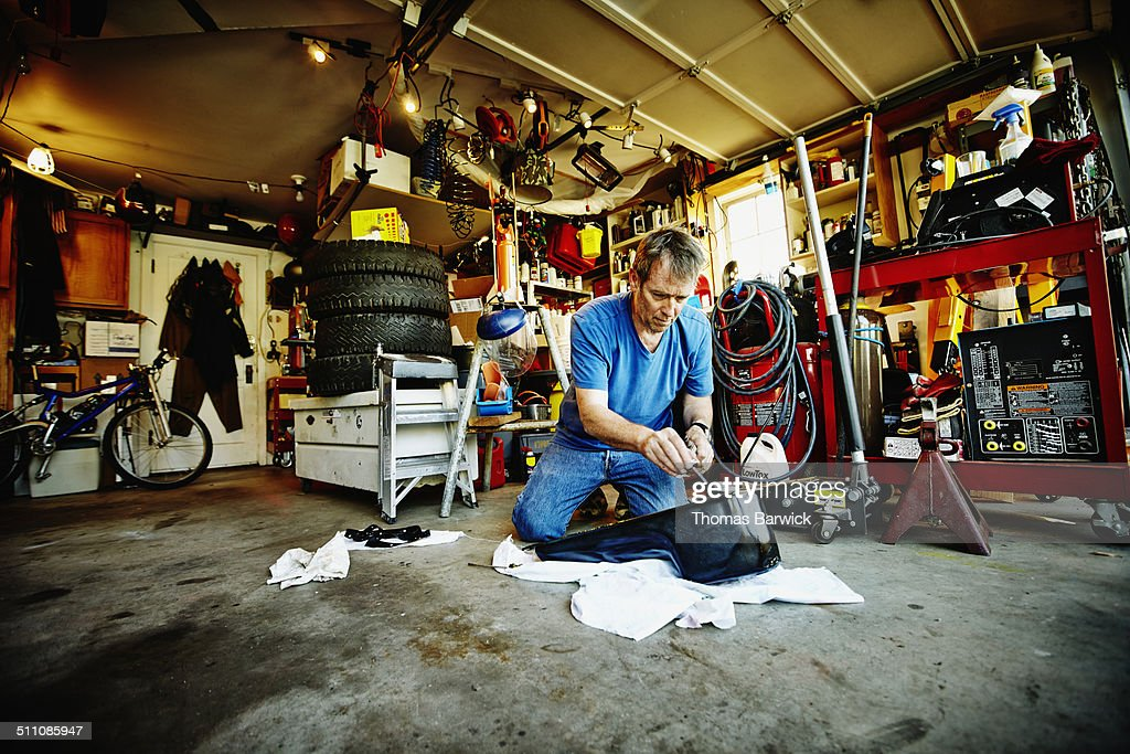 man in garage working on oil pan of vehicle stock photo