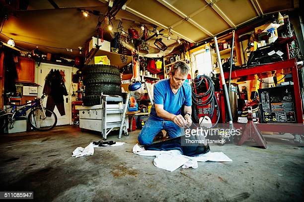 Man in garage working on oil pan of vehicle