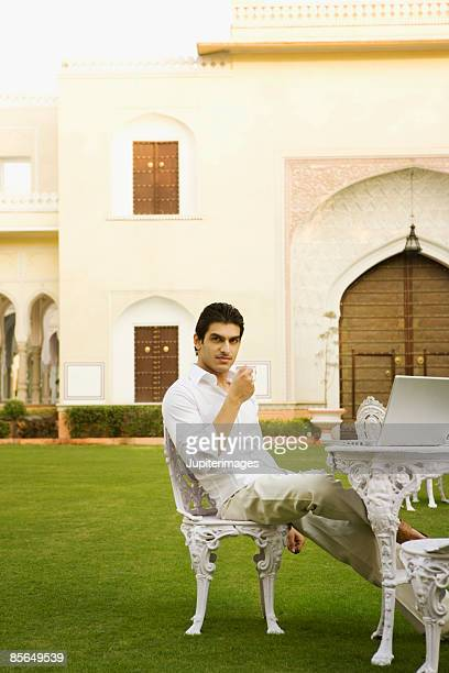 Man in garden with beverage and laptop computer, India