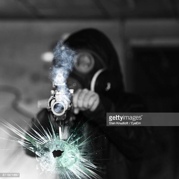 Man in gas mask shooting a glass