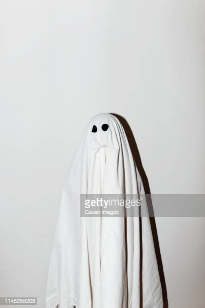 man in ghost costume standing against wall - ghost stock pictures, royalty-free photos & images