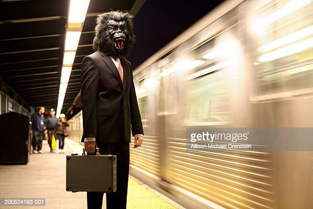 man in gorilla mask waiting for train - monkey suit stock pictures, royalty-free photos & images