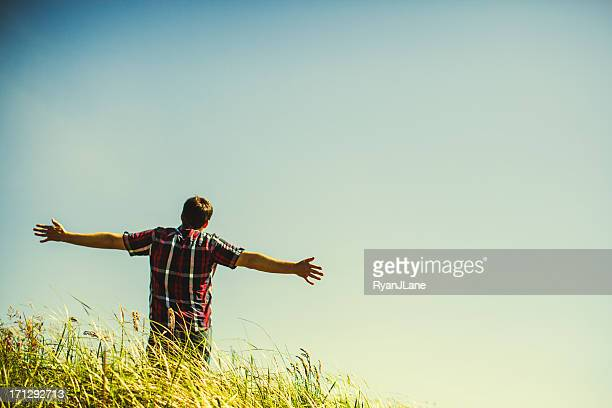 man in grass field enjoying nature - place of worship stock pictures, royalty-free photos & images