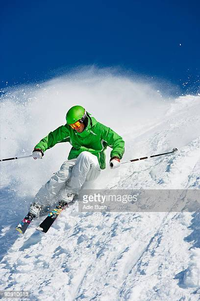 Man in green carving off piste.