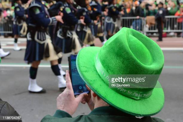 Man in green hat, recording St. Patrick's Day Parade on his iPhone.