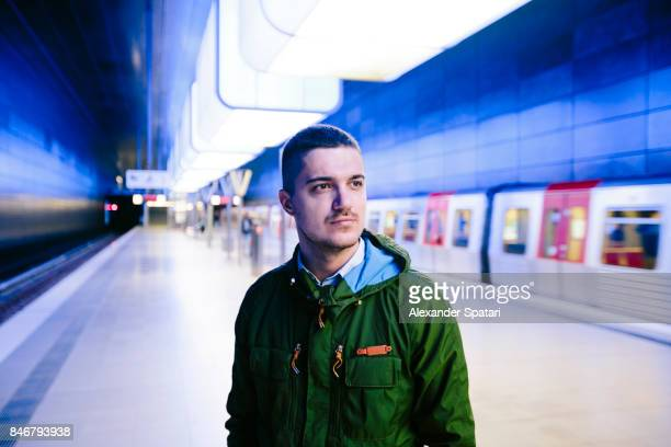 Man in green jacket standing on a subway platfrom with blue lighting
