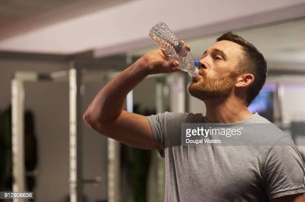 man in gym drinking water. - dougal waters stock pictures, royalty-free photos & images