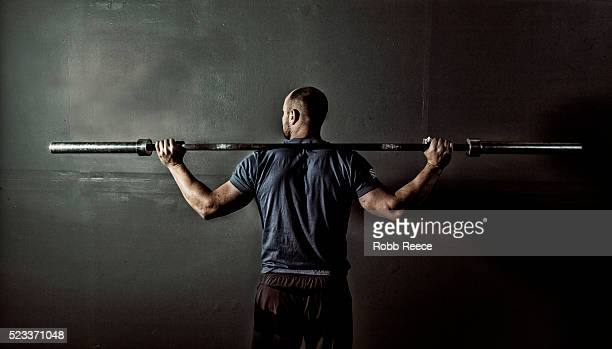 man in gym gym with weight bar on shoulders - robb reece stockfoto's en -beelden