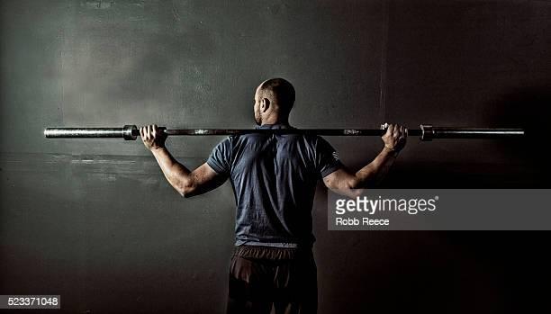 man in gym gym with weight bar on shoulders - robb reece fotografías e imágenes de stock