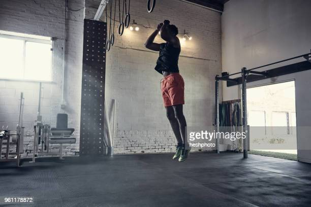 man in gym jumping in mid air - heshphoto photos et images de collection