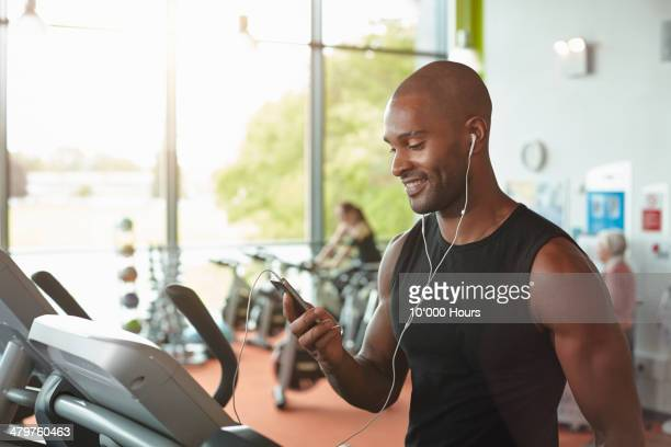 Man in gym on treadmill looking at smart phone