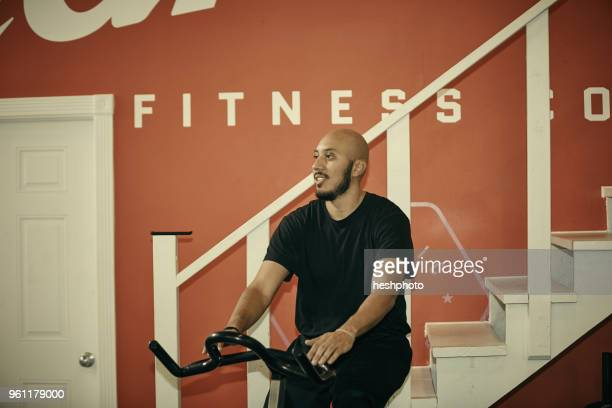 man in gym using exercise bike - heshphoto stockfoto's en -beelden