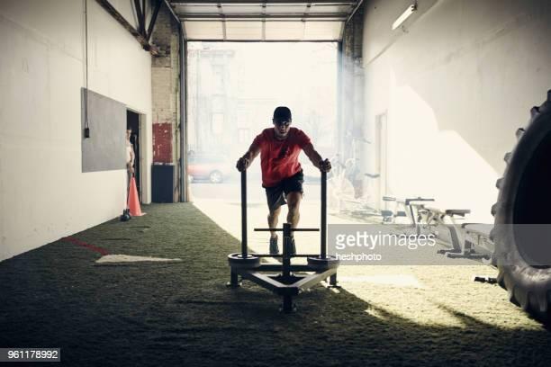 man in gym using exercise equipment - heshphoto stock-fotos und bilder
