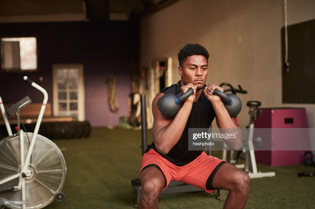 Man in gym using kettle bells : Stock Photo
