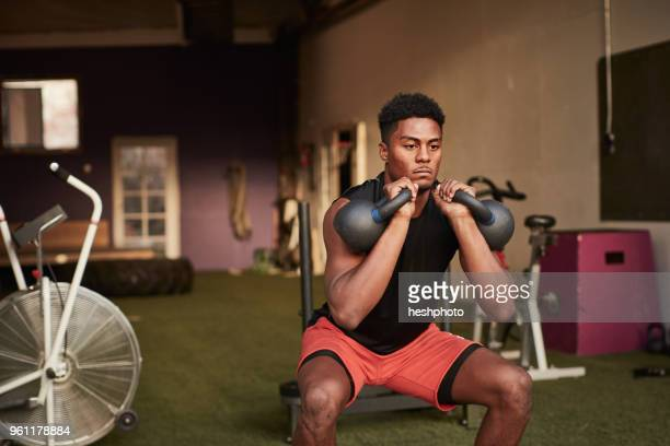 man in gym using kettle bells - heshphoto stock pictures, royalty-free photos & images