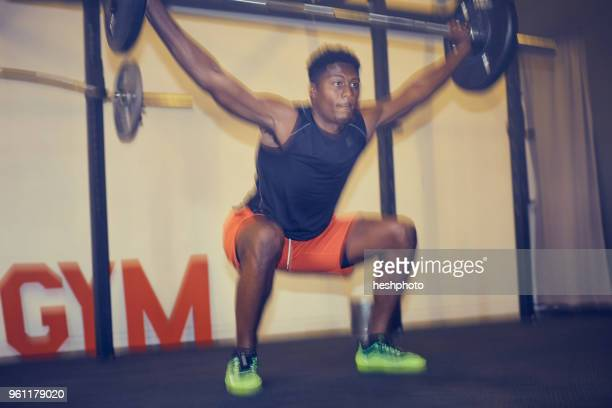 man in gym weightlifting using barbell, defocused - heshphoto stockfoto's en -beelden