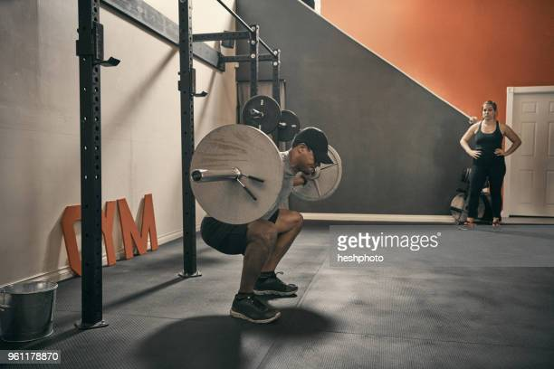 man in gym weightlifting using barbell - heshphoto stockfoto's en -beelden