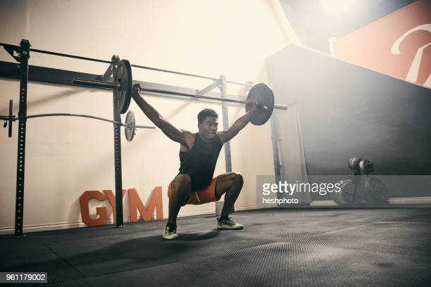 man in gym weightlifting using barbell - heshphoto stock pictures, royalty-free photos & images