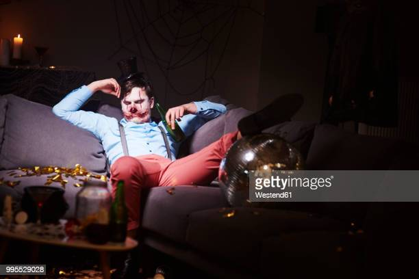 man in halloween costume sleeping on couch after party - after party man stock pictures, royalty-free photos & images