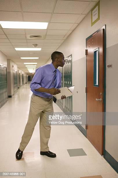 Man in hallway holding folder, looking into classroom